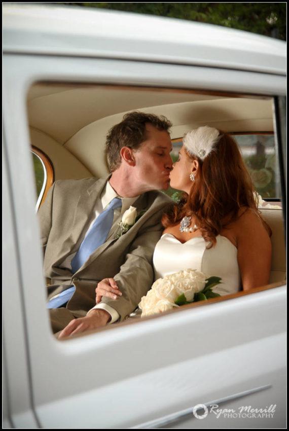 bride & Groom kissing in a classic car Wedding Photos